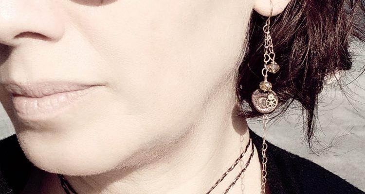 la foto mostra un paio di orecchini artigianali a pendente indossati